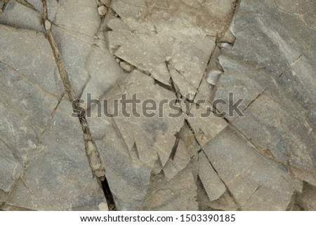 Gray rough rough rock with large cracks. #1503390185