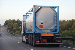 Gray semi truck tanker with 80/2586 dangerous class sign on barrel drive on asphalt highway on a summer day on green trees background, Arylsulfonic acids ADR hazardous cargo logistics, rear view