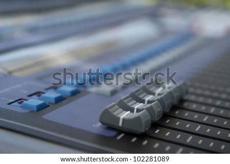 Gray slider on a sound mixer with blurry background