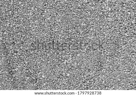 Photo of  Gray small rocks ground texture. black small road stone background. gravel pebbles stone seamless texture, marble. dark background of crushed granite gravel, close up. grey clumping clay