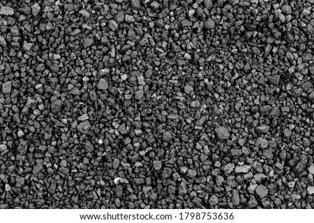 Photo of  Gray small rocks ground texture. black small road stone background. gravel pebbles stone seamless texture. dark background of crushed granite gravel, close up. clumping clay