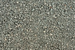 Gray small rocks ground texture. black small road stone background. gravel pebbles stone texture. dark background of crushed granite gravel, close up. clumping clay