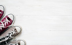 Gray sneakers and claret sneaker on white wooden floor background, top view