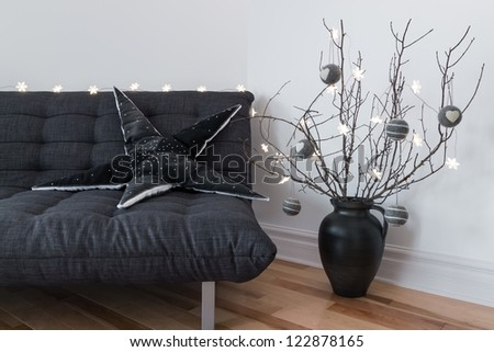 Gray sofa, winter decorations and cozy lights in the living room.