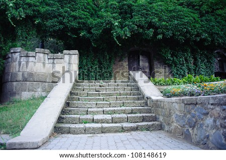 Gray solid stone stairs to the black door