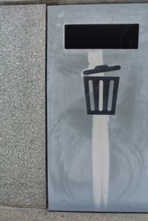 Gray stainless steel garbage bin next to the cement wall