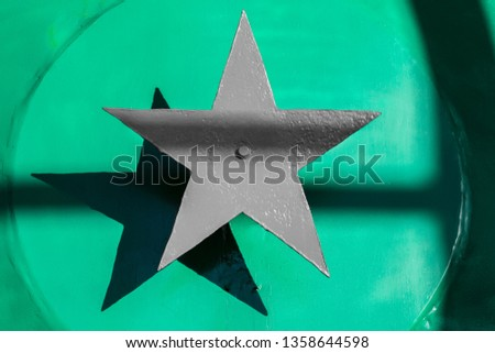 Gray steel five-pointed star on a green background