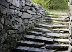 Gray stone stairs with large stone side walls lead to below ground passage way.