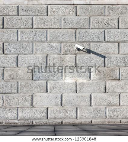 gray stone wall and security camera - stock photo