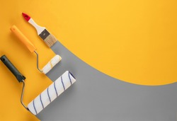 Gray stripes of paint from rollers and brushe on a yellow background. Home renovation concept.