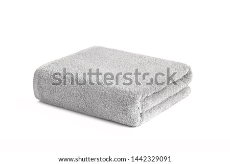 Gray terry towel folded and stacked isolated. Terry towel against white backdrop. Folded soft bath towel. Cotton towel on a white background
