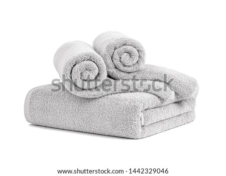 Gray terry towels rolled, folded and stacked isolated.Terry towels against white backdrop. Folded and rolled soft bath towels. Stack of grey cotton towels on a white background