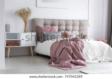 Gray tufted headboard and pink bedcover in simple bedroom with minimalist interior design and copper accessories #747042289