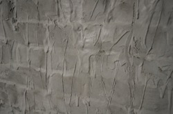 Gray uneven wall of background or texture with spots and lines from the trowel or spatula, streams of liquid glue. Close up uneven plaster surface. Wall banner or design for the label