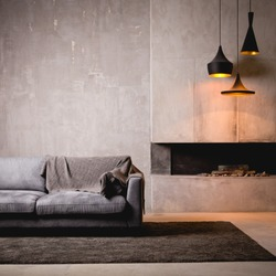 Gray velour sofa in a dark room the bright light from eternal light, and artificial fireplace. Interior loft with concrete walls