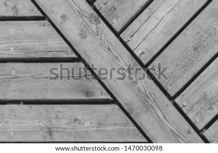 Gray weathered wood boards. Wooden planks on a floor or deck with grain and screws. Flat head head screw in wood
