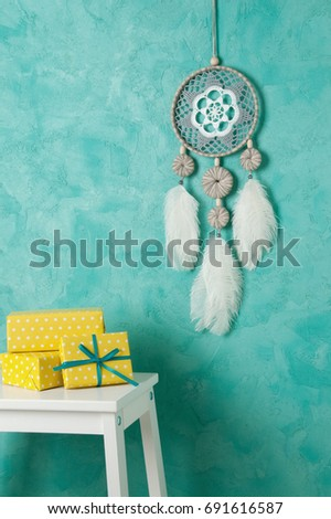 Gray white dream catcher , white bedside table and yellow white polka dot boxes in bedroom interior on aquamarine textured background. Copy space for text and gift ideas. #691616587