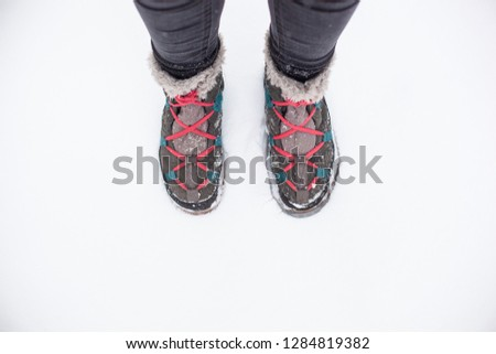 Gray winter boots with fur and blue stripes laced up with pink laces in the snow #1284819382