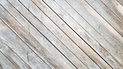 Gray wooden background with diagonal lines. Board background with copy space. Wooden old boards with cracked gray paint on the diagonal. Selective focus. Textured wooden background.