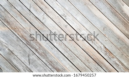 Photo of  Gray wooden background with diagonal lines. Board background with copy space. Wooden old boards with cracked gray paint on the diagonal. Selective focus. Textured wooden background.