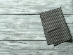 Gray wooden table with balck and white dark linen kitchen towel or textile napkin flat lay. Dark tablecloth on old gray wood tabletop. Copy space for text. Can use as mock up for design.