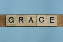 gray word grace in small square wooden letters with black font on a blue background