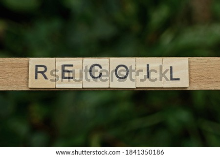 Photo of  gray word recoil made of wooden square letters on green background