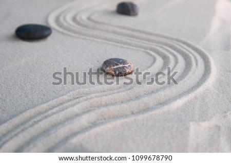 Gray zen stones on light sand. Concept of harmony, balance and meditation, spa, massage, relax