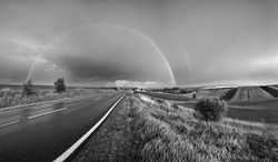 Grayscale. Spring rapeseed and small farmlands fields after rain evening view, cloudy pre sunset sky with rainbow and rural hills. Seasonal, weather, climate, eco, farming, countryside beauty concept.