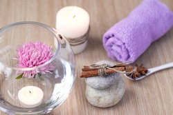 Graystones on top of each other, a candle, a lilac rolled towel, a vase of water with a lilac flower and candles floating in the water, cinnamon and star anise. Spa setting concept. Soft focus