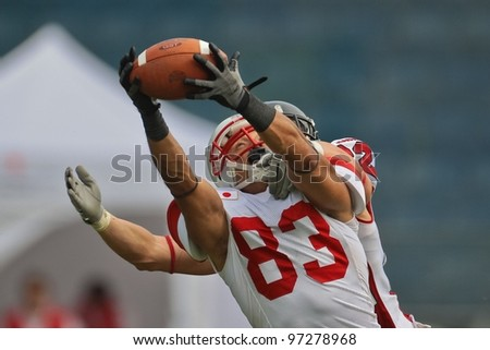 GRAZ, AUSTRIA - JULY 13 WR Ken Shimizu (#83 Japan) catches the ball at the Football World Championship on July 13, 2011 in Graz, Austria. Canada wins 31:27 against Japan. - stock photo