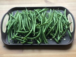 Grean beans in a trey on a wooden table