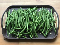 Grean beans in a trey on a wooden table - close up