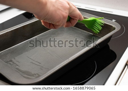greasing baking sheet with oil. Cooking a cake tin Foto d'archivio ©