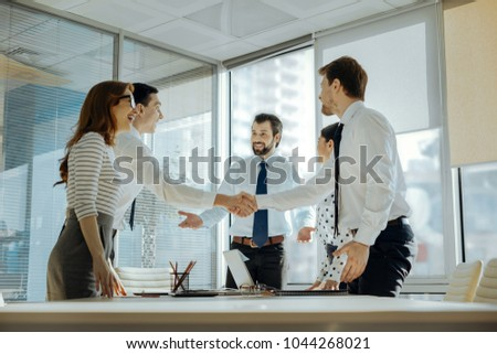 Great achievement. Upbeat young employees smiling brightly and shaking each others hands while congratulating each other with the successful project