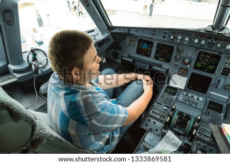 great amazing view of a young adolescent pilot student sitting in passenger air plane cockpit during taring session  #1333869581