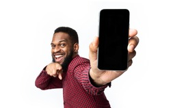 Great App. African Man Showing Phone Blank Screen Recommending New Mobile Application Posing Over White Studio Background, Smiling To Camera. Apps Advertisement With Smartphone Display Mockup