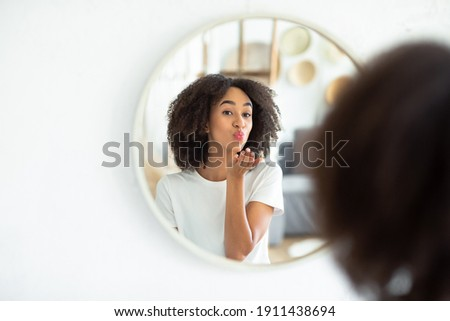 Great appearance, love yourself and perfect skin. Cheerful young african american lady makes air kiss and looks in reflection of round mirror in living room, on white wall, panorama, free space Foto stock ©