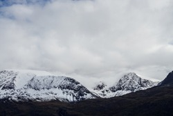 Great black mountains with white snow on tops and glaciers. Dramatic landscape with snowy mountains under cloudy gray sky. Atmospheric alpine scenery with snow on rocky mountains in overcast weather.