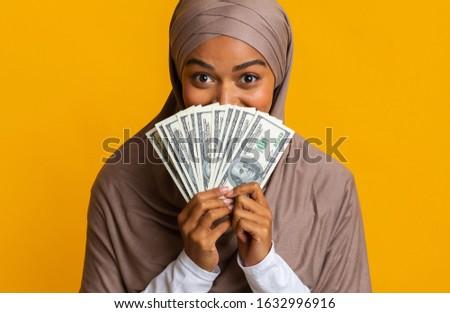 Great Bonus. Portrait Of Joyful Afro Islamic Woman In Hijab Hiding Face Behind Dollar Cash Fan In Her Hands