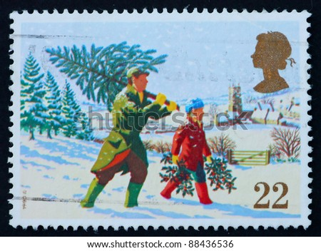 GREAT BRITAIN - CIRCA 1990: a stamp printed in the Great Britain shows Father and child carrying Christmas tree, Christmas, circa 1990