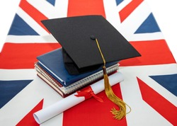 Great Britain education. Graduation diploma and academic graduate hat on the UK flag background. Great Britain education.