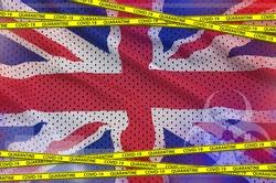 Great britain flag and Covid-19 quarantine yellow tape. Coronavirus or 2019-nCov virus concept