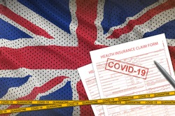 Great britain flag and Health insurance claim form with covid-19 stamp. Coronavirus or 2019-nCov virus concept