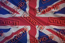Great britain flag and many red Covid-19 stamps. Coronavirus or 2019-nCov virus concept