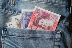 Great Britain pound banknotes in back pocket of blue jeans