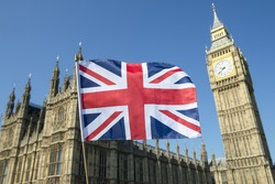 Great British Union Jack flag flying in front of Big Ben and the Houses of Parliament at Westminster Palace, London, a symbol of national pride during the EU Brexit and election proceedings
