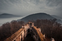 great castle ruins in the Palatinate Forest.  photographed from above from a tower with thick fog in the valleys and clouds in the sky