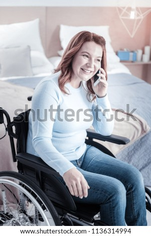 Stock Photo Great day. Cheerful female person keeping smile on her face while talking per telephone