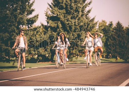 Great day for cycling. Group of young people riding bicycles along a road and looking happy #484943746